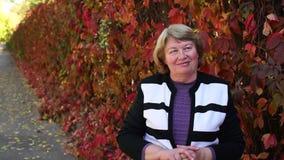 Πορτρέτο μιας ηλικιωμένης γυναίκας στο πάρκο φθινοπώρου ενάντια στα κόκκινα δέντρα απόθεμα βίντεο