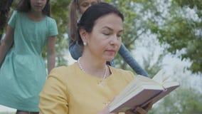 Πορτρέτο μιας κομψής ανώτερης γυναίκας που διαβάζει το βιβλίο στο πάρκο στο πρώτο πλάνο Δύο κορίτσια που γλιστρούν επάνω πίσω, έν απόθεμα βίντεο