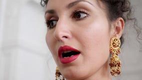Πορτρέτο μιας κομψής νέας γυναίκας με τα κόκκινα χείλια στα όμορφα κομψά σκουλαρίκια απόθεμα βίντεο