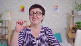 Πορτρέτο μιας κουφής χαμογελώντας γυναίκας που κρατά μια συνεδρίαση ενίσχυσης ακρόασης στο καθιστικό απόθεμα βίντεο