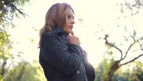 Πορτρέτο μιας κρύας γυναίκας σε ένα πάρκο φθινοπώρου το κορίτσι φτερνίζεται και τυλίγεται σε ένα μαντίλι απόθεμα βίντεο
