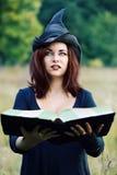 Πορτρέτο μιας μάγισσας με ένα βιβλίο Στοκ Φωτογραφία