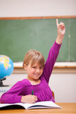 Πορτρέτο μιας μαθήτριας που αυξάνει το χέρι της στοκ εικόνες