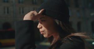 Πορτρέτο μιας νέας γυναίκας αφροαμερικάνων που περιμένει ένα ταξί ή ένα λεωφορείο, υπαίθρια απόθεμα βίντεο