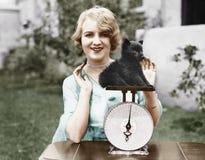 Πορτρέτο μιας νέας γυναίκας που ζυγίζει το κουτάβι της σε έναν ζυγό (όλα τα πρόσωπα που απεικονίζονται δεν ζουν περισσότερο και κ Στοκ εικόνες με δικαίωμα ελεύθερης χρήσης