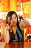 Πορτρέτο μιας νέας γυναίκας που κρατά μια μπύρα με ένα χέρι και τα κλειδιά αυτοκινήτων της με την άλλο χέρι, στο υπόβαθρο φραγμών Στοκ Φωτογραφία
