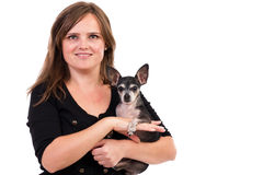 Πορτρέτο μιας νέας γυναίκας που κρατά το σκυλί κατοικίδιων ζώων της. Στοκ Φωτογραφίες