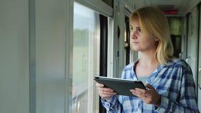 Πορτρέτο μιας νέας γυναίκας που οδηγά ένα τραίνο, που απολαμβάνει μια ταμπλέτα Πάντα στην αφή απόθεμα βίντεο