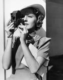 Πορτρέτο μιας νέας γυναίκας που παίρνει μια εικόνα με μια κάμερα (όλα τα πρόσωπα που απεικονίζονται δεν ζουν περισσότερο και κανέ Στοκ Εικόνα