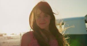 Πορτρέτο μιας νέας γυναίκας που στέκεται σε μια παραλία που χαμογελά 4k απόθεμα βίντεο