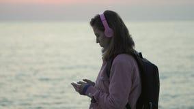 Πορτρέτο μιας νέας γυναίκας που στέκεται στην παραλία με ένα smartphone και απόθεμα βίντεο