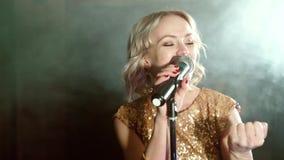 Πορτρέτο μιας νέας γυναίκας που τραγουδά σε ένα σκοτεινό καπνώές δωμάτιο απόθεμα βίντεο
