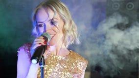 Πορτρέτο μιας νέας γυναίκας που τραγουδά σε ένα σκοτεινό καπνώές δωμάτιο φιλμ μικρού μήκους