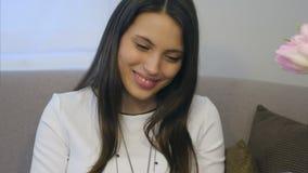 Πορτρέτο μιας νέας γυναίκας που χαμογελά, διαβάζοντας τα μηνύματα από το φίλο στον υπολογιστή ταμπλετών στον καναπέ φιλμ μικρού μήκους