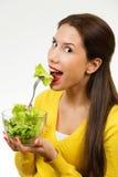 Πορτρέτο μιας νέας γυναίκας, που χαμογελά και που τρώει ένα κύπελλο της σαλάτας στοκ φωτογραφίες