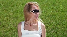 Πορτρέτο μιας νέας γυναίκας σε έναν πράσινο χορτοτάπητα απόθεμα βίντεο