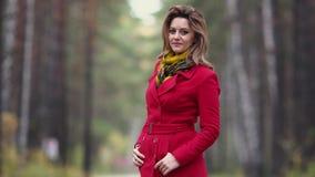 Πορτρέτο μιας νέας γυναίκας σε ένα πάρκο φθινοπώρου όμορφο κορίτσι στο κόκκινο παλτό που θέτει και που χαμογελά στη κάμερα φιλμ μικρού μήκους