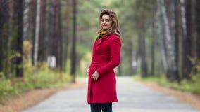 Πορτρέτο μιας νέας γυναίκας σε ένα πάρκο φθινοπώρου όμορφο κορίτσι στο κόκκινο παλτό που θέτει και που χαμογελά στη κάμερα απόθεμα βίντεο