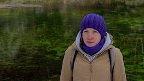 Πορτρέτο μιας νέας γυναίκας σε ένα υπόβαθρο της πράσινης λίμνης απόθεμα βίντεο