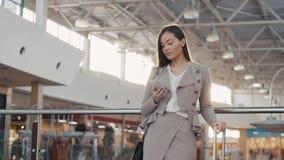 Πορτρέτο μιας νέας γυναίκας τουριστών εφήβων που επισκέπτεται την πόλη που ψωνίζει χρησιμοποιώντας τη συσκευή και το χαμόγελο sma Στοκ Φωτογραφία