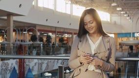 Πορτρέτο μιας νέας γυναίκας τουριστών εφήβων που επισκέπτεται την πόλη που ψωνίζει χρησιμοποιώντας τη συσκευή και το χαμόγελο sma Στοκ Εικόνες