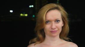 Πορτρέτο μιας νέας γυναίκας χωρίς σύνθεση με τους γυμνούς ώμους ενάντια στα μουτζουρωμένα φω'τα της πόλης διάστημα αντιγράφων απόθεμα βίντεο