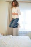 Πορτρέτο μιας νέας ευτυχούς γυναίκας που πηδά στο κρεβάτι στοκ εικόνες με δικαίωμα ελεύθερης χρήσης