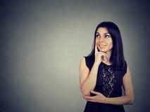 Πορτρέτο μιας νέας ευτυχούς γυναίκας που χαμογελά και που σκέφτεται στοκ φωτογραφίες
