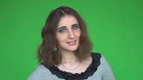 Πορτρέτο μιας νέας ευτυχούς τοποθέτησης γυναικών σε ένα μετακινούμενο βασικό κλίμα χρώματος απόθεμα βίντεο