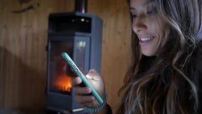 Πορτρέτο μιας νέας ελκυστικής μικτής γυναίκας φυλών που χαμογελά και που χρησιμοποιεί το κινητό τηλέφωνο κοντά στην εστία Άνετος  φιλμ μικρού μήκους