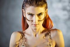 Πορτρέτο μιας νέας μοντέρνης γυναίκας με τα χρυσά μοσχεύματα στο πρόσωπό της Μεταλλικά makeup και φρύδια στοκ εικόνες με δικαίωμα ελεύθερης χρήσης