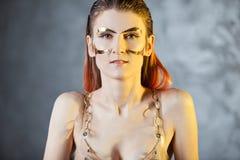 Πορτρέτο μιας νέας μοντέρνης γυναίκας με τα χρυσά μοσχεύματα στο πρόσωπό της Μεταλλικά makeup και φρύδια στοκ εικόνα