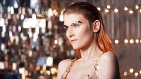 Πορτρέτο μιας νέας μοντέρνης γυναίκας με τα χρυσά μοσχεύματα στο πρόσωπό της Μεταλλικά makeup και φρύδια στοκ φωτογραφίες