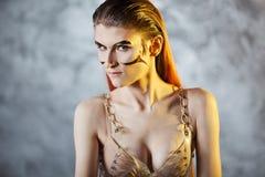 Πορτρέτο μιας νέας μοντέρνης γυναίκας με τα χρυσά μοσχεύματα στο πρόσωπό της Μεταλλικά makeup και φρύδια στοκ εικόνα με δικαίωμα ελεύθερης χρήσης