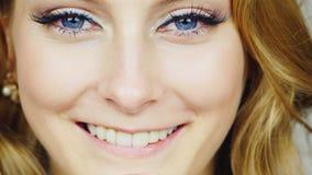 Πορτρέτο μιας νέας μπλε-eyed γυναίκας που κτυπά το πρόσωπό της με τα άκρα δακτύλου του φιλμ μικρού μήκους