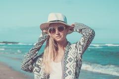 Πορτρέτο μιας νέας προκλητικής γυναίκας με το άσπρο καπέλο και των γυαλιών ηλίου που περπατούν στην άσπρη παραλία άμμου ένα τροπι Στοκ Φωτογραφίες