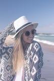 Πορτρέτο μιας νέας προκλητικής γυναίκας με το άσπρο καπέλο και των γυαλιών ηλίου που περπατούν στην άσπρη παραλία άμμου ένα τροπι Στοκ εικόνα με δικαίωμα ελεύθερης χρήσης