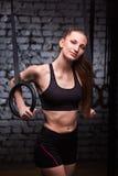 Πορτρέτο μιας νέας φίλαθλης γυναίκας στα μαύρα sportwear όπλα κατάρτισης με τα δαχτυλίδια γυμναστικής ενάντια στο τουβλότοιχο Στοκ Εικόνες