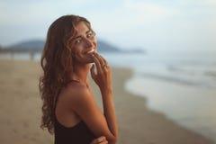 Πορτρέτο μιας νέας όμορφης γυναίκας με τη μακριά σγουρή τρίχα στην παραλία στοκ φωτογραφία