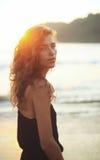 Πορτρέτο μιας νέας όμορφης γυναίκας με τη μακριά σγουρή τρίχα στην παραλία στοκ εικόνα
