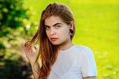 Πορτρέτο μιας νέας όμορφης γυναίκας με τις ξύλινες σήραγγες στα αυτιά της Στοκ εικόνα με δικαίωμα ελεύθερης χρήσης