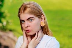 Πορτρέτο μιας νέας όμορφης γυναίκας με τις ξύλινες σήραγγες στο ε της Στοκ φωτογραφίες με δικαίωμα ελεύθερης χρήσης