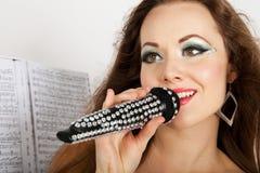Πορτρέτο μιας νέας όμορφης γυναίκας στο μαύρο τραγούδι φορεμάτων στοκ εικόνες