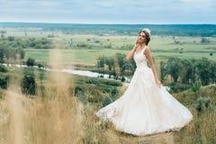Πορτρέτο μιας νέας όμορφης νύφης σε ένα υπόβαθρο μιας πανέμορφης άποψης του ποταμού και των τομέων Στοκ Εικόνες