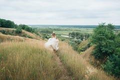 Πορτρέτο μιας νέας όμορφης νύφης σε ένα υπόβαθρο μιας πανέμορφης άποψης του ποταμού και των τομέων Στοκ Φωτογραφία