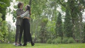 Πορτρέτο μιας νεολαίας που αγκαλιάζει το αγαπώντας ζεύγος που έχει το υπόλοιπο σε ένα πάρκο Ζεύγος ημερομηνίας υπαίθρια απόθεμα βίντεο