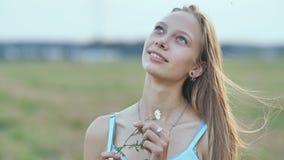 Πορτρέτο μιας νεολαίας που χαμογελά το 16χρονο κορίτσι με ένα λουλούδι μαργαριτών στα χέρια της ξανθό τρίχωμα μακρύ φιλμ μικρού μήκους