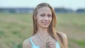 Πορτρέτο μιας νεολαίας που χαμογελά το 16χρονο κορίτσι με ένα λουλούδι μαργαριτών στα χέρια της ξανθό τρίχωμα μακρύ απόθεμα βίντεο