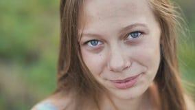 Πορτρέτο μιας νεολαίας που χαμογελά το 16χρονο κορίτσι με ένα λουλούδι μαργαριτών στα χέρια της Καφετής-μαλλιαρό κορίτσι με μακρυ φιλμ μικρού μήκους