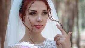 Πορτρέτο μιας νύφης σε ένα δάσος, σε ένα γαμήλιο φόρεμα που αγγίζει μια μπούκλα της τρίχας της, κινηματογράφηση σε πρώτο πλάνο, σ απόθεμα βίντεο